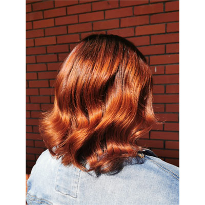 Femme montrant le look total effet cuivré dans ses cheveux