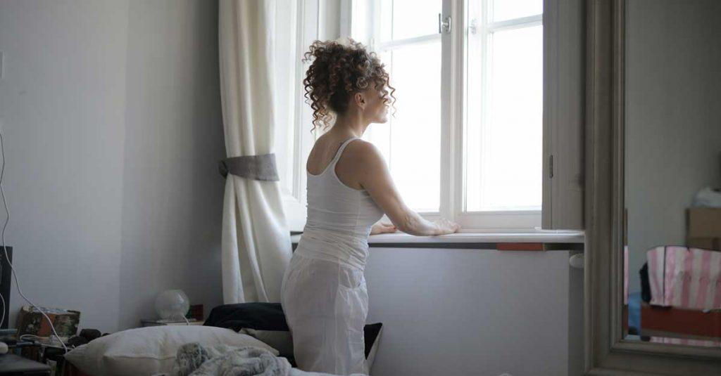 Femme avec des cheveux bouclés regardant par la fenêtre