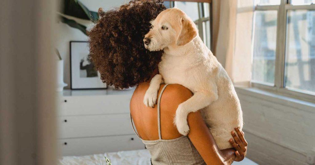 Femme avec des cheveux bouclés tenant son chien