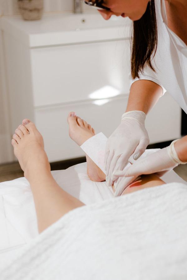 Femme en train de se faire épiler les jambes par une esthéticienne