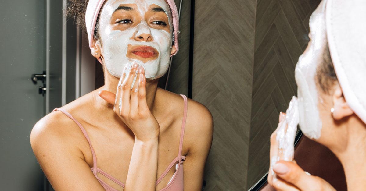 Routine de soin du visage l'été - Femme en train d'appliquer un exfoliant